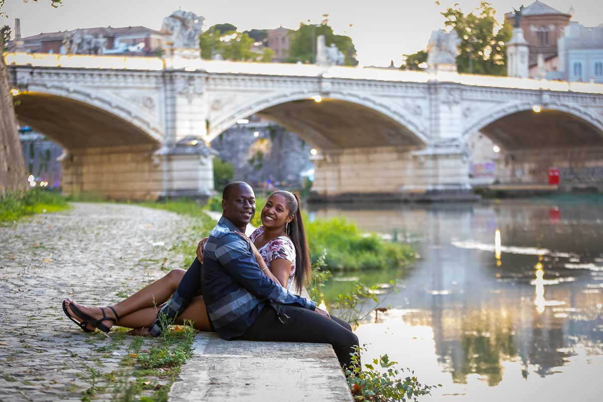 Couple posing while sitting down next to the river water with lit bridge behind them