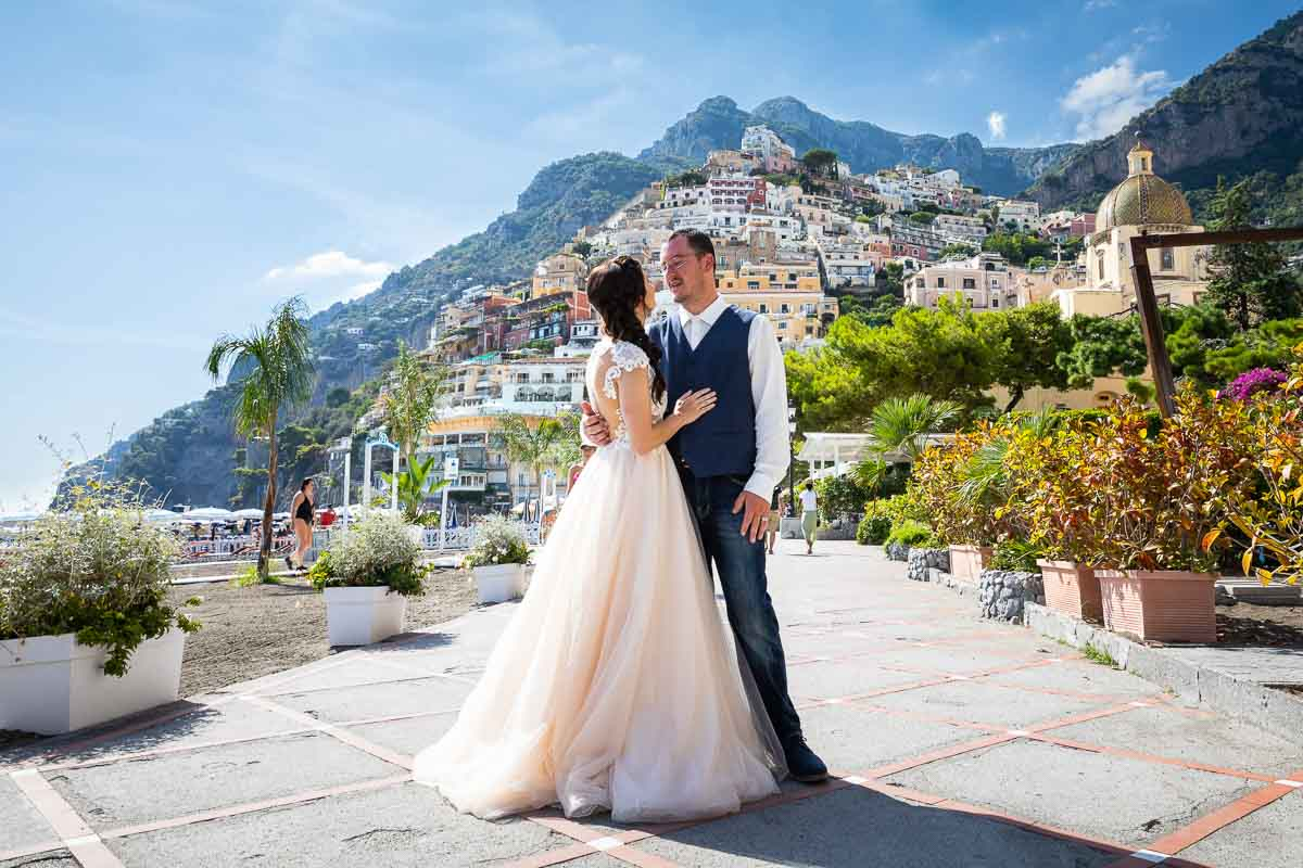 Bride and groom posing together on the boardwalk beach of the town of Positano in the heart of the Amalfi coast. Image by the Andrea Matone photographer studio