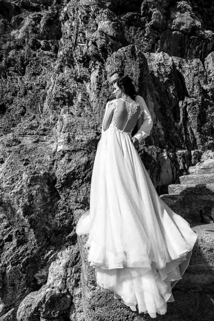 Bridal dress photography in black and white photographed against the rocks