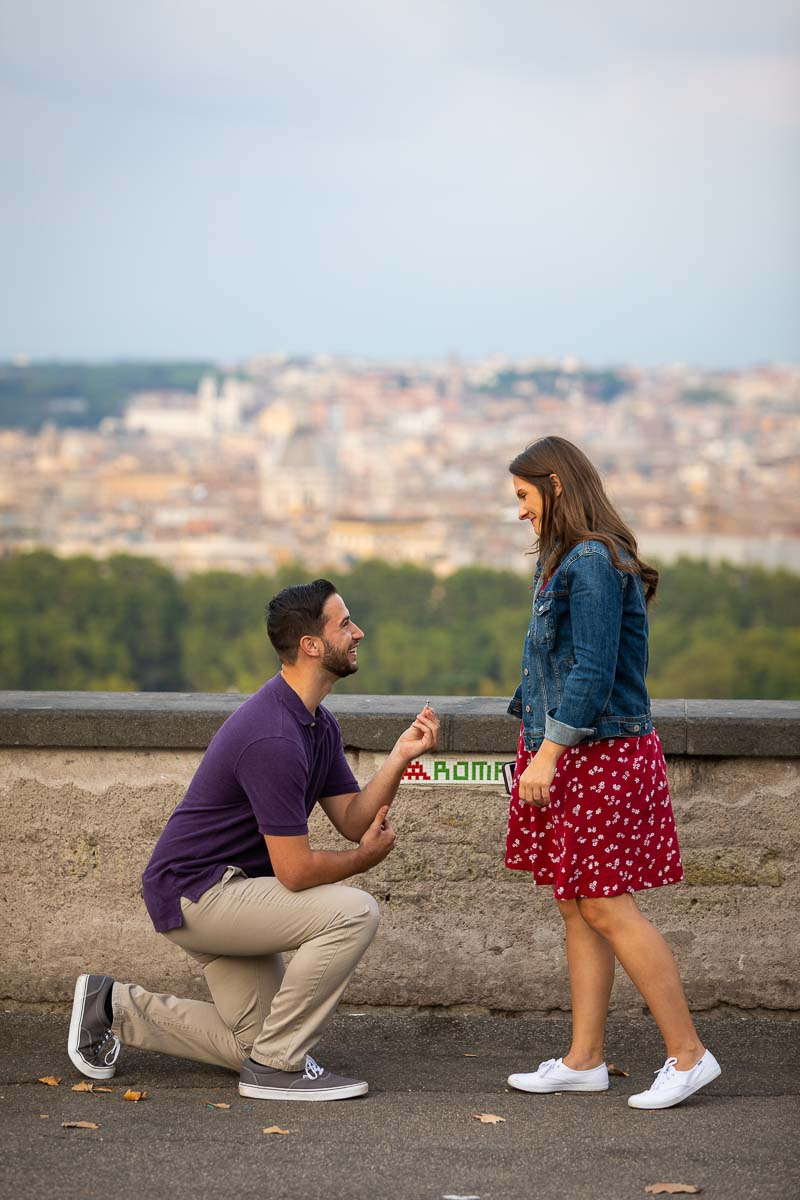 Kneed own wedding marriage proposal taking place on the Janiculum hill overlooking the city of Rome from a nearby hill