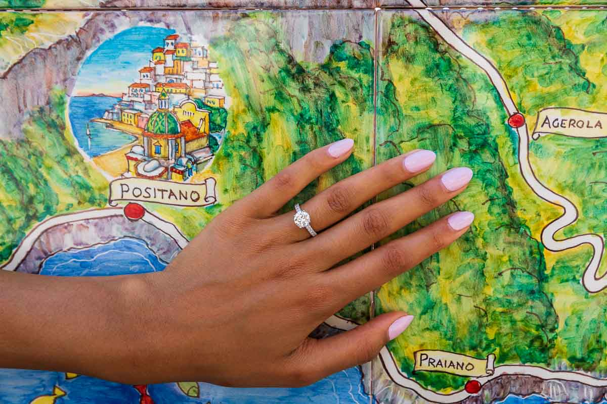 Close up of the engagement ring posed in front of the Positano ceramic map