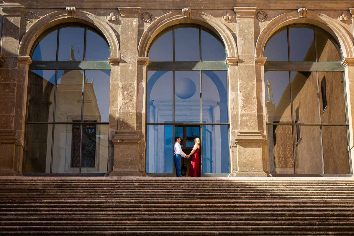 Holding hands together and standing underneath the staircase entrance of Campidoglio in Rome Italy