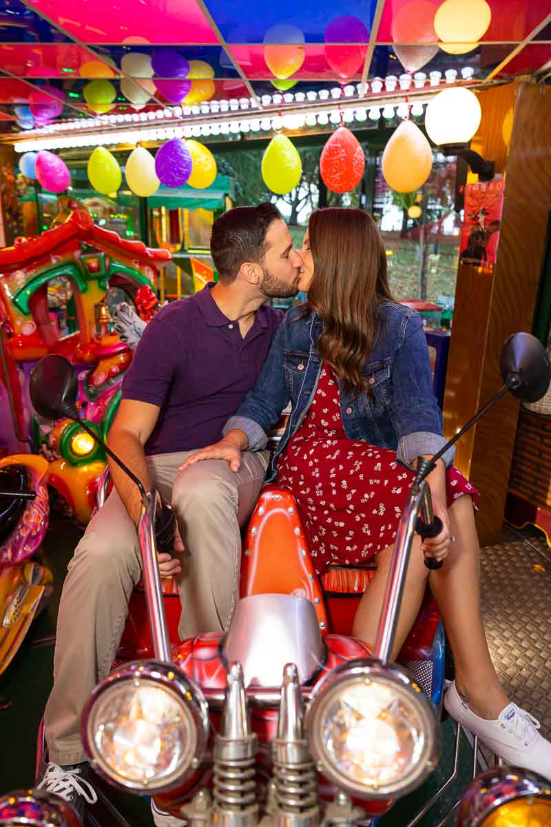 Couple kissing on an amusement ride of a motorcycle for two