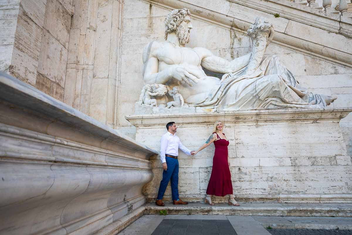 Walking picture of a couple leading while photographed underneath a large marble roman statue