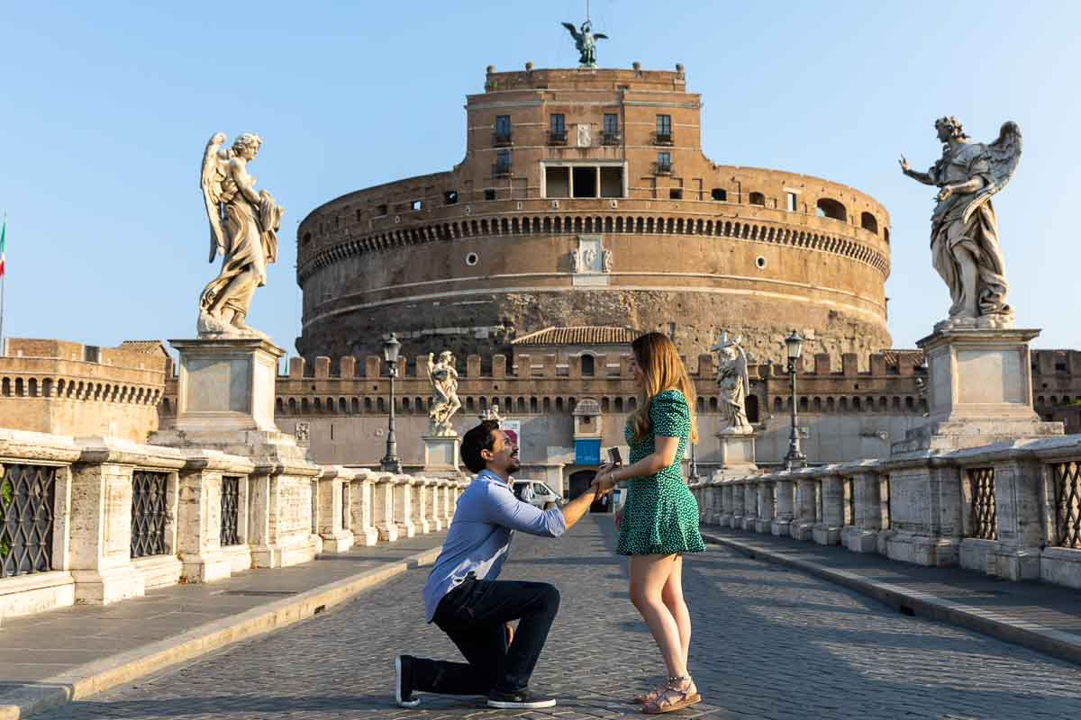 Man knee down wedding marriage proposal photography on Rome's Angel Castle bridge in the early morning. Castel Sant'angelo Bridge Proposal photography