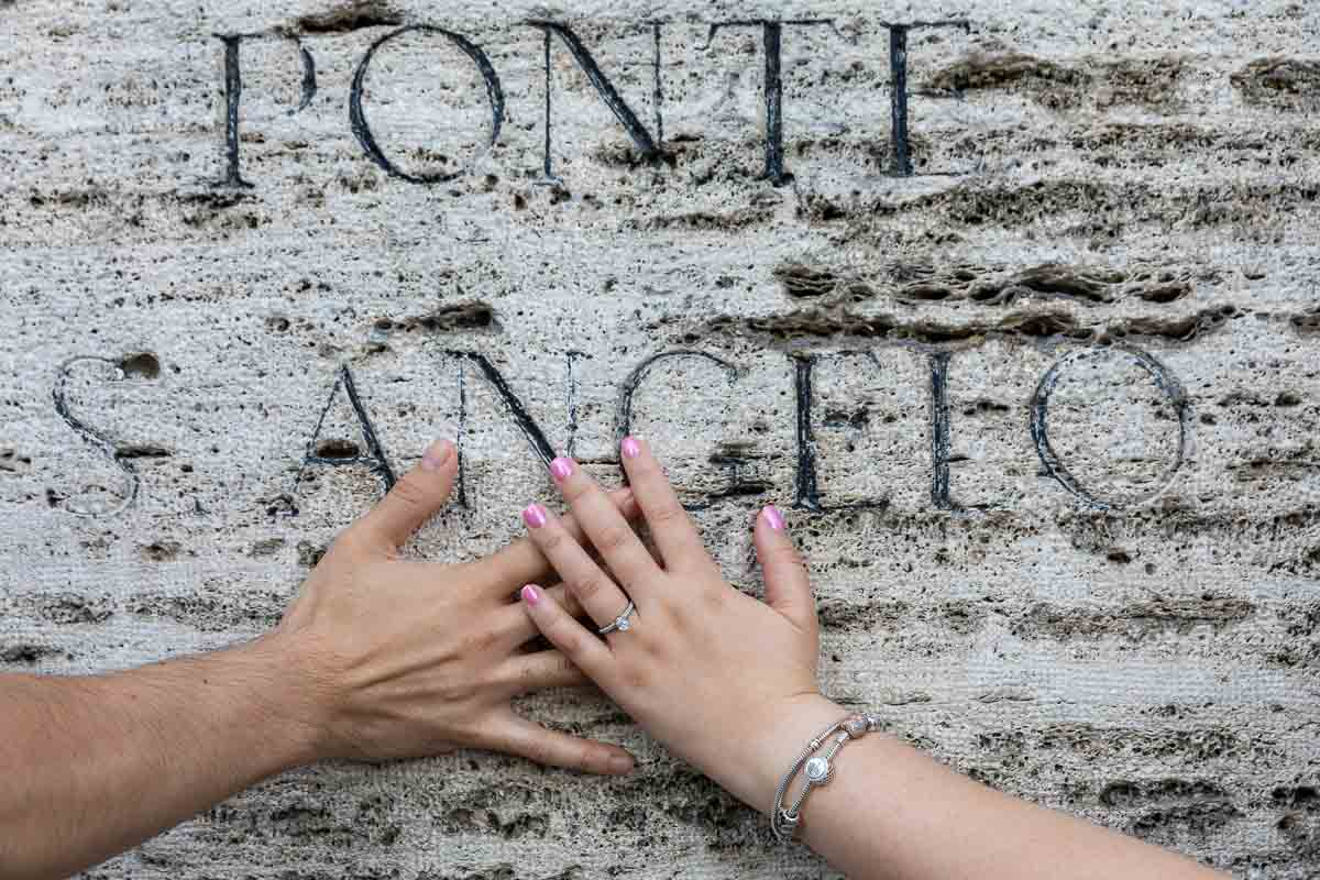 Close up of the engagement ring worn on the hand on top of the ancient marble sign