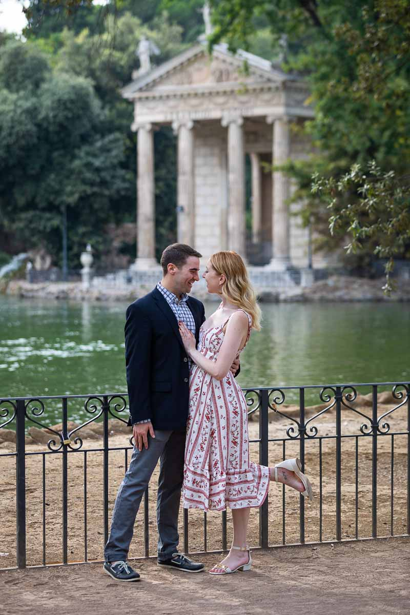 Couple in love inRome before the ancient temple in the middle of the borghese park lake