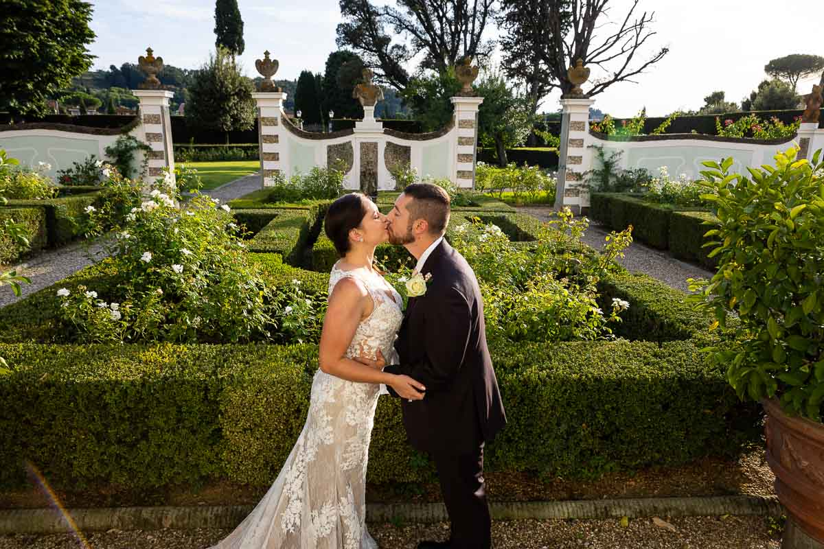 Newlyweds kissing on the beautiful Italian style gardens