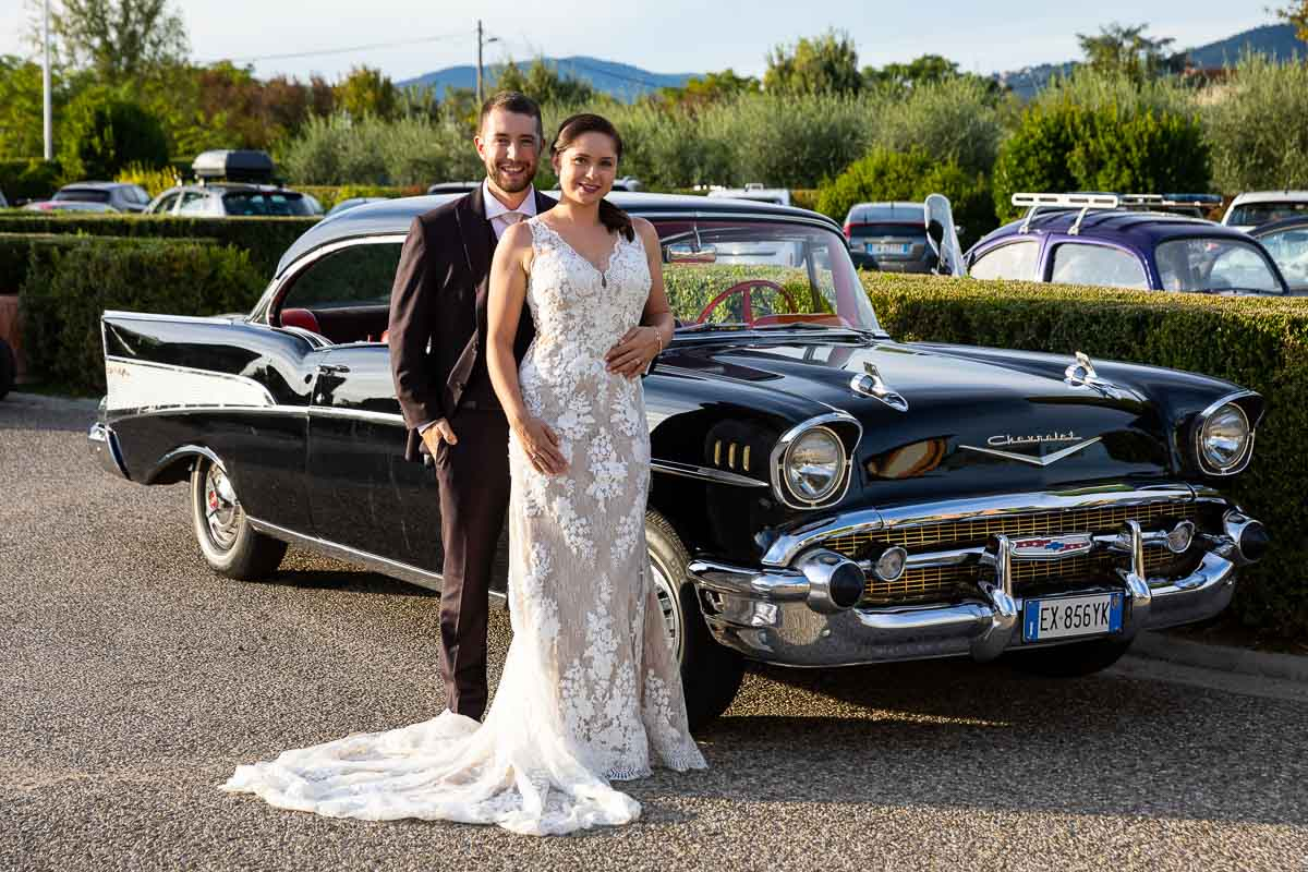 Bride and groom portrait picture taken next to a black Cadillac