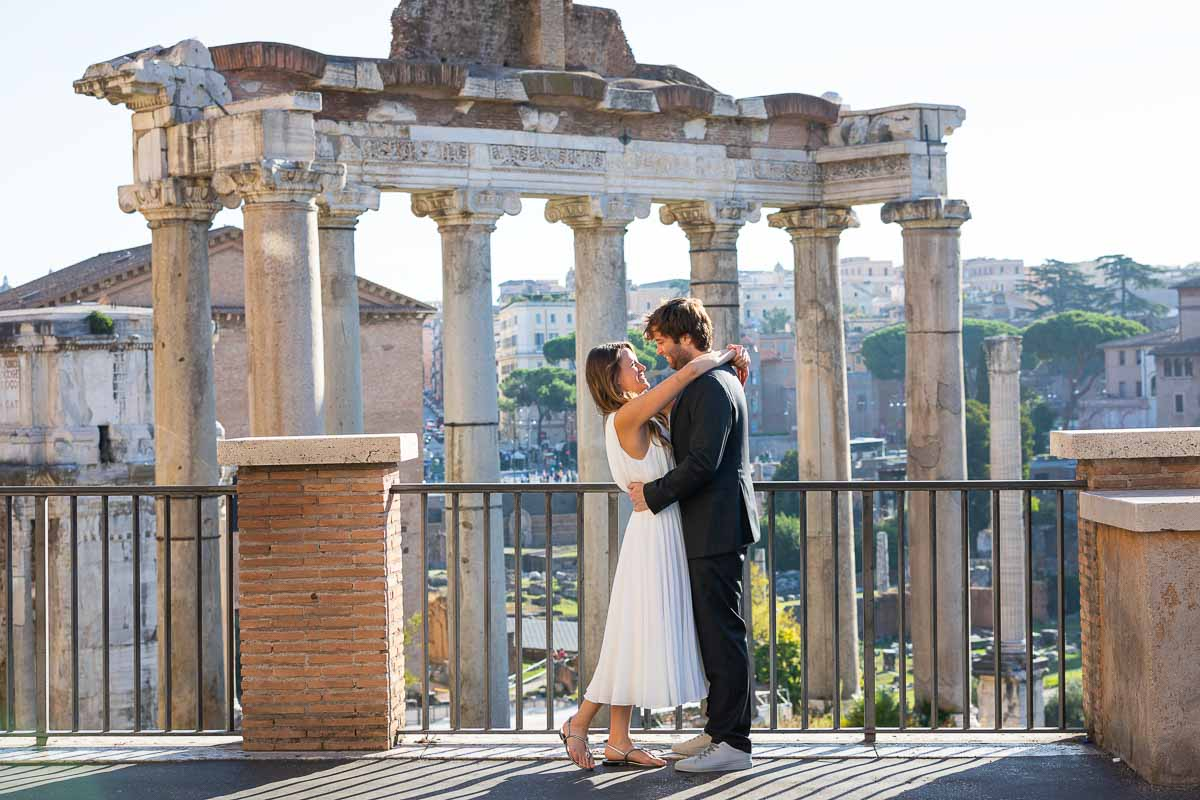 Taking pictures posed together at the Roman Forum with the ancient Rome city in the background