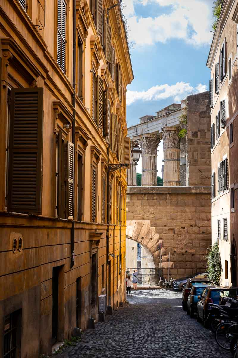 Roman alleyway street with the ancient imperial forum in the far backdrop. Rome, Italy