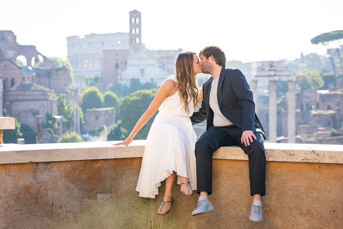 Couple kissing during a wedding photography service before the sweeping view of the roman ruins