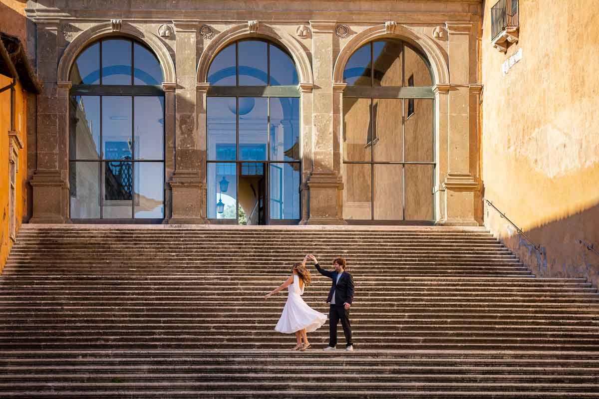 Newlyweds practicing dance moves on a wide staircase during a couple photoshoot