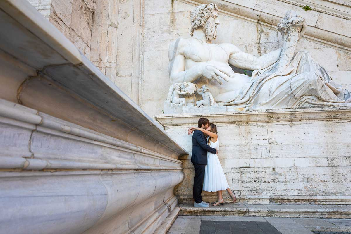 Posed image of groom and bride kissing underneath a large white marble roman statue