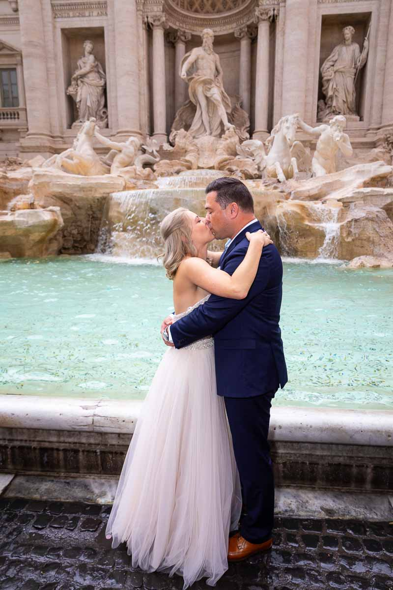Newlywed couple kissing in front of the Trevi fountain