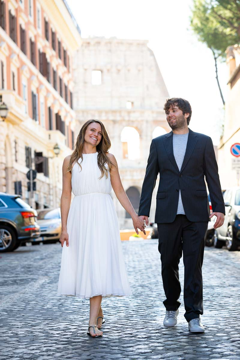 Newlyweds walking together and strolling the roman streets with the unique and iconic monument in the background