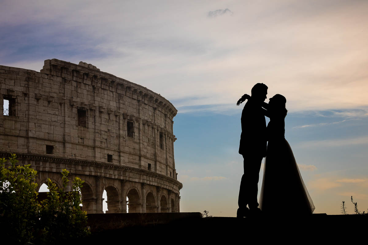 Newlyweds taking photos at the Roman Colosseum during a photo shoot