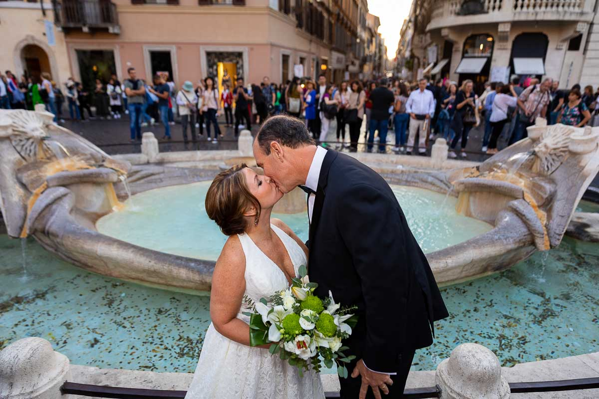 Couple kissing down below by the Barcaccia water fountain found at the bottom of the Spanish steps