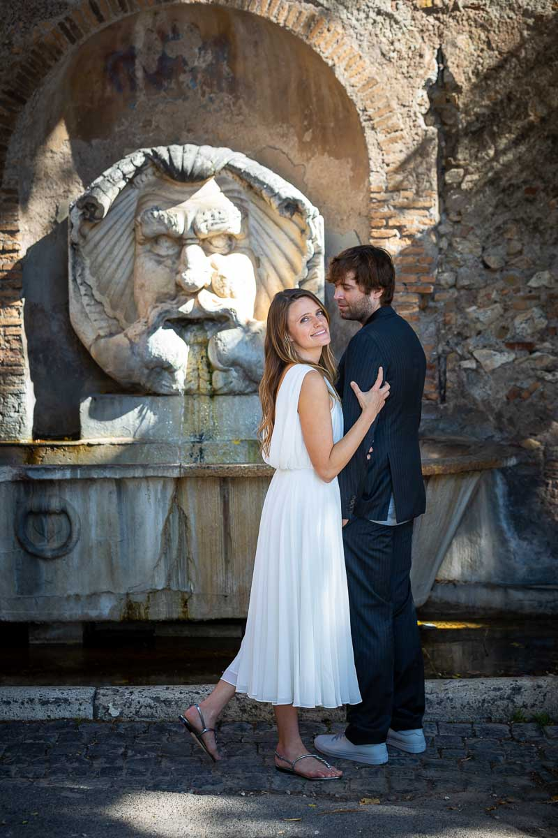 Couple picture pose in front of the marble water fountain found at the entrance of Rome' Giardino degli Aranci