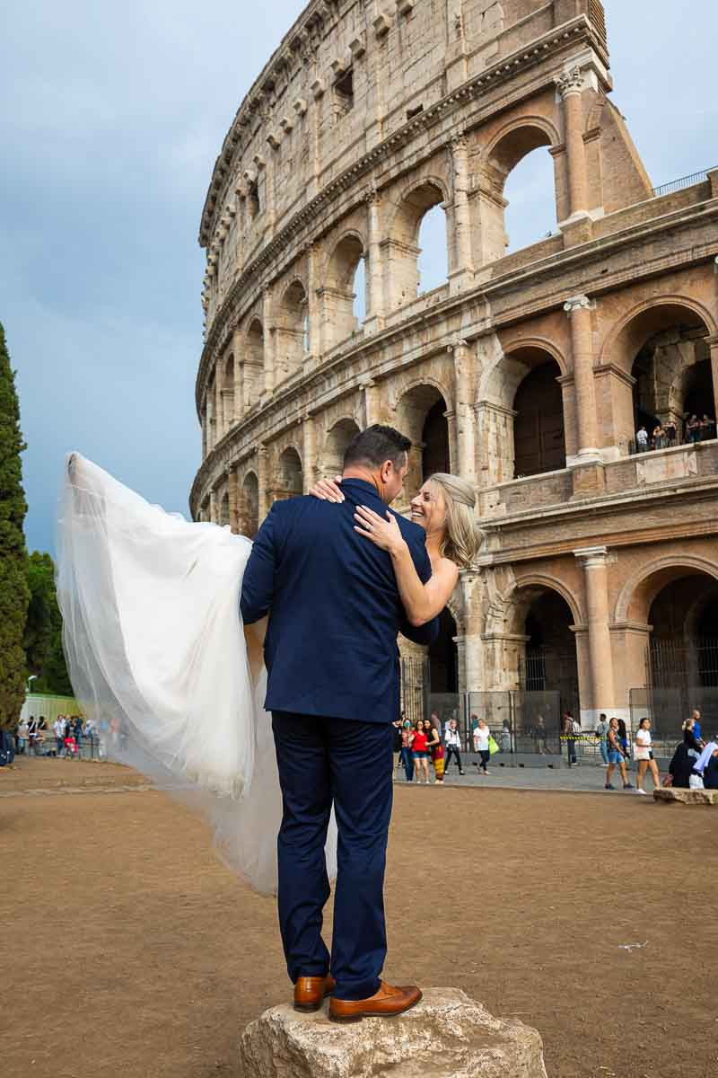Groom picking up the bride in front of the Coliseum