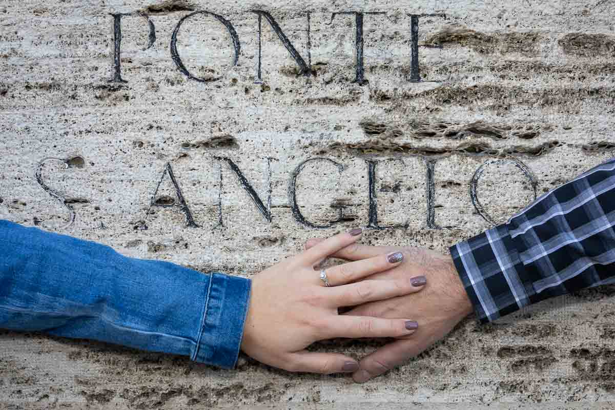 Photo of overlapping hands showing the beautiful engagement ring photographed against peperino rock with the name of ponte s. angelo