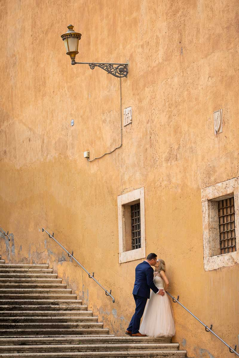 Portrait picture of the newlywed couple on a large set of stairs under roman light post
