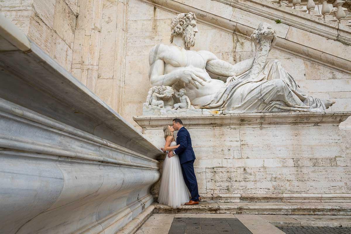Kissing underneath a large white marble roman statue at Piazza del Campidoglio