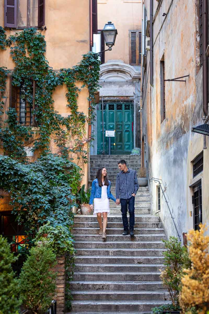 Couple walking hand in hand during an engagement photo shoot in the streets of Rome Italy