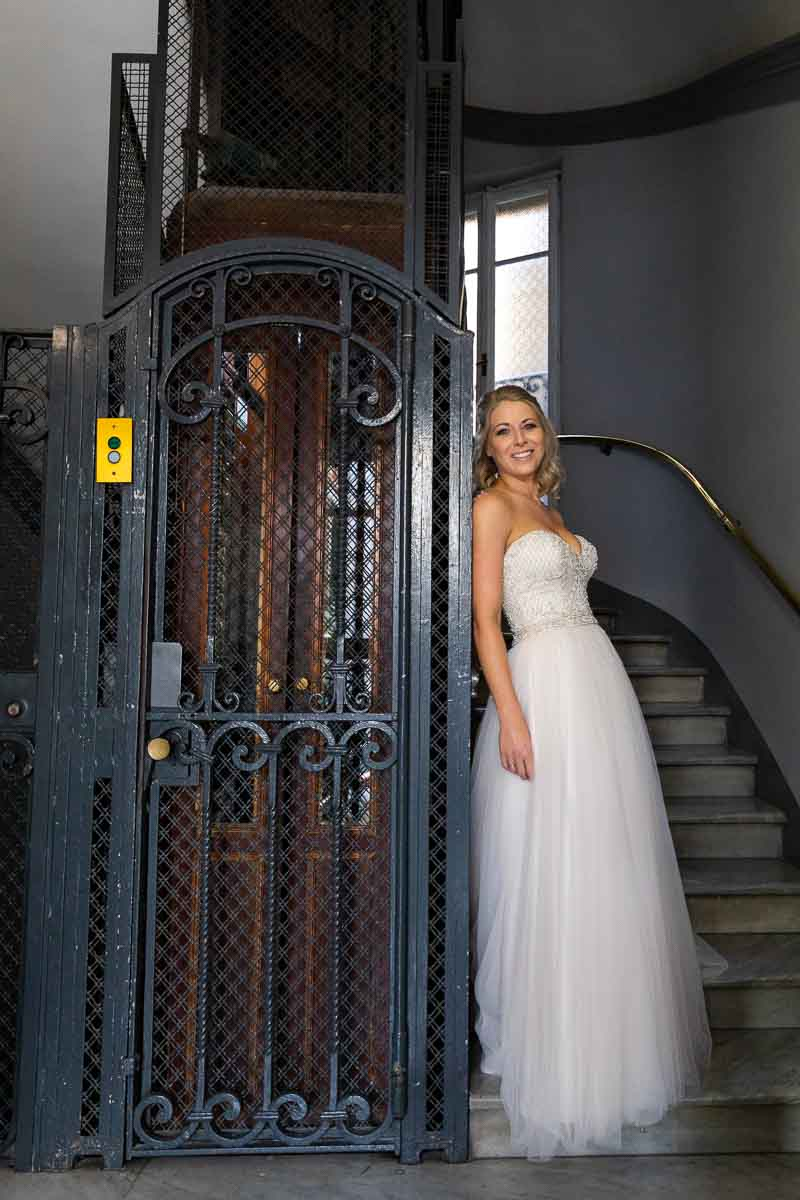 Bride posed next to an iron elevator in nice natural light