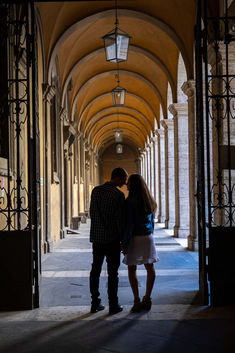 Silhouette image of a recently engaged couple posing by the cloister portico