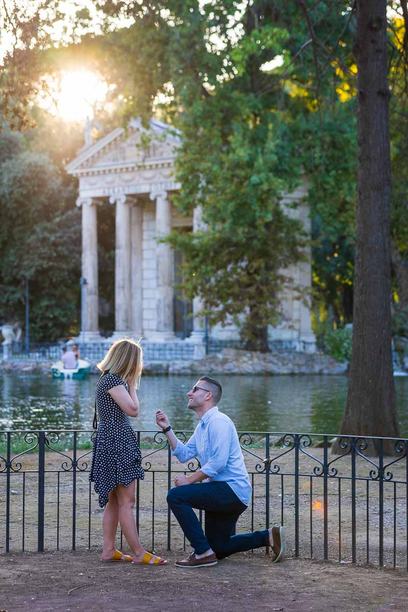 Lakeside wedding marriage proposal candidly photographed from a distance in Rome's Villa Borghese park