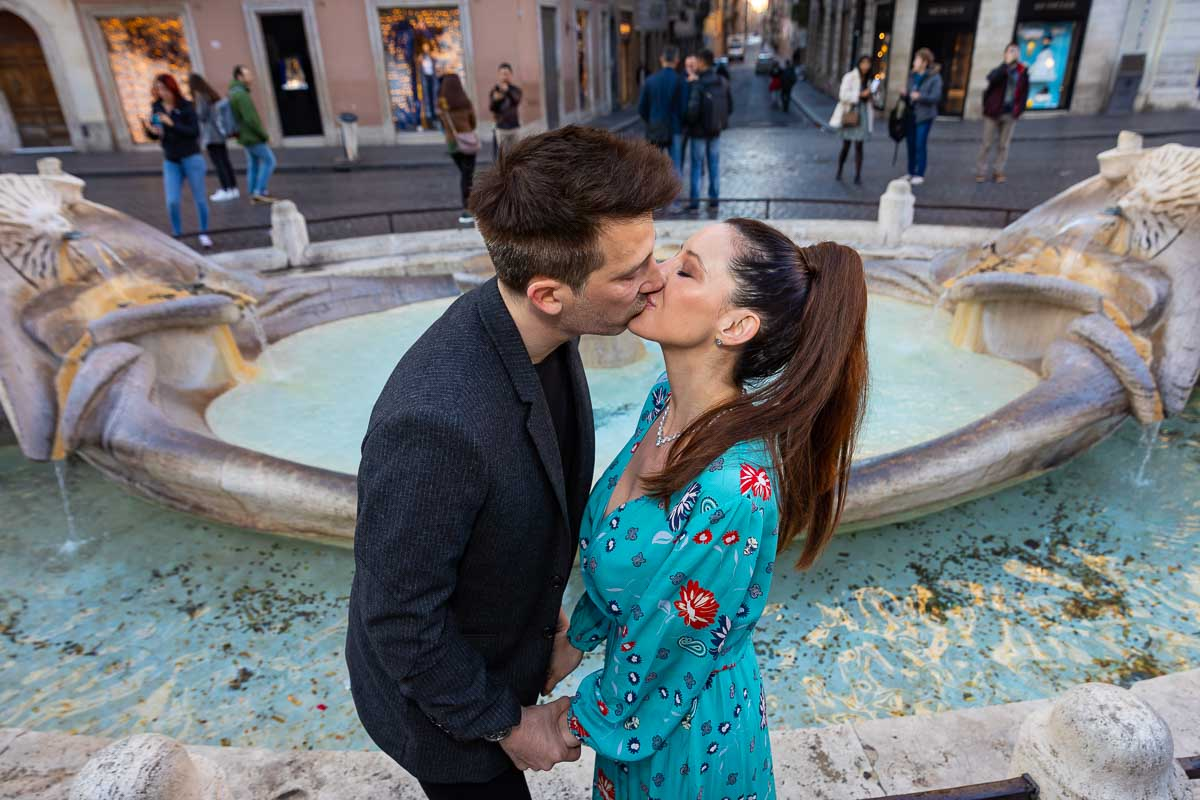 Kissing each other in front of the water fountain found at the bottom of the Spanish steps