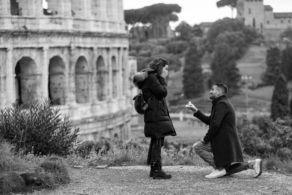Knee down surprise wedding proposal photographed at the Roman Coliseum with black and white image processing