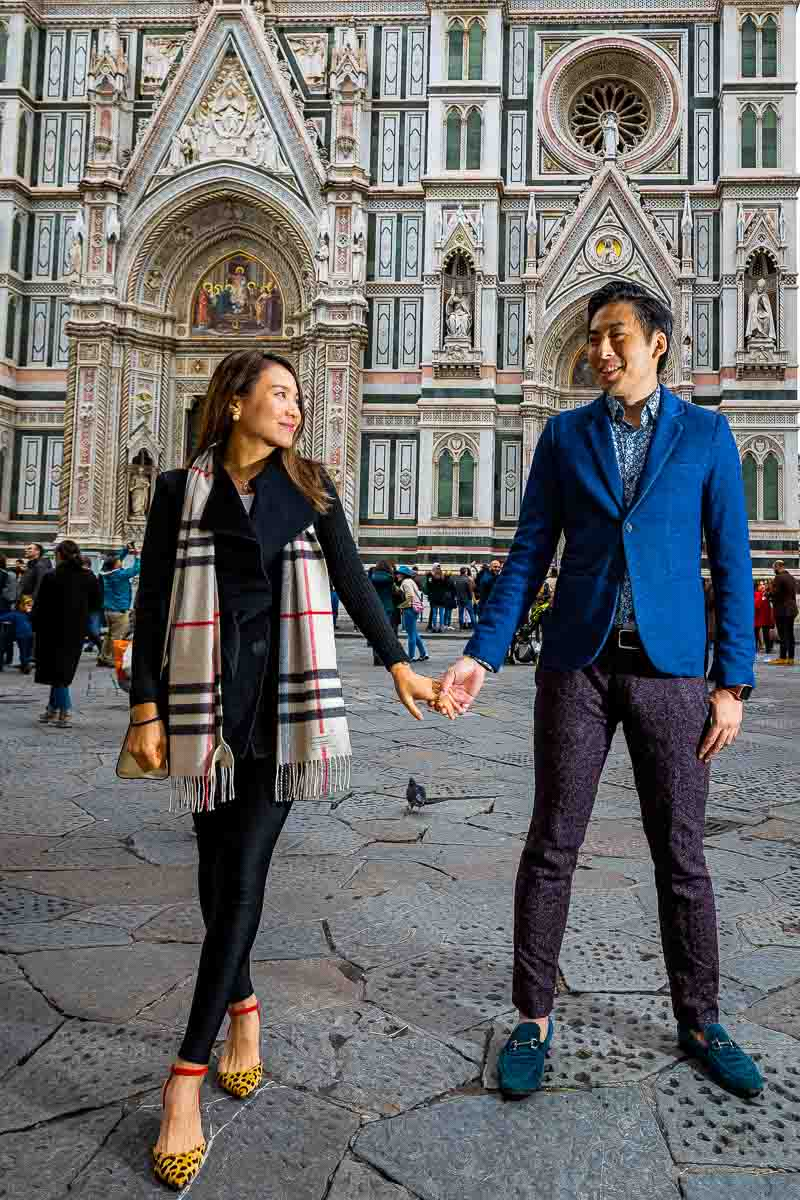Couple standing and holding hands in front of Cathedral of Santa Maria del Fiore in Florence Italy