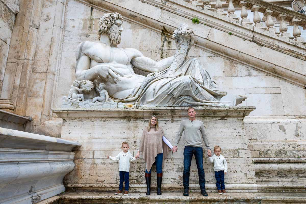 Family portrait photography taken underneath an ancient marble roman statue in the heart of Rome Italy in Piazza del Campidolgio