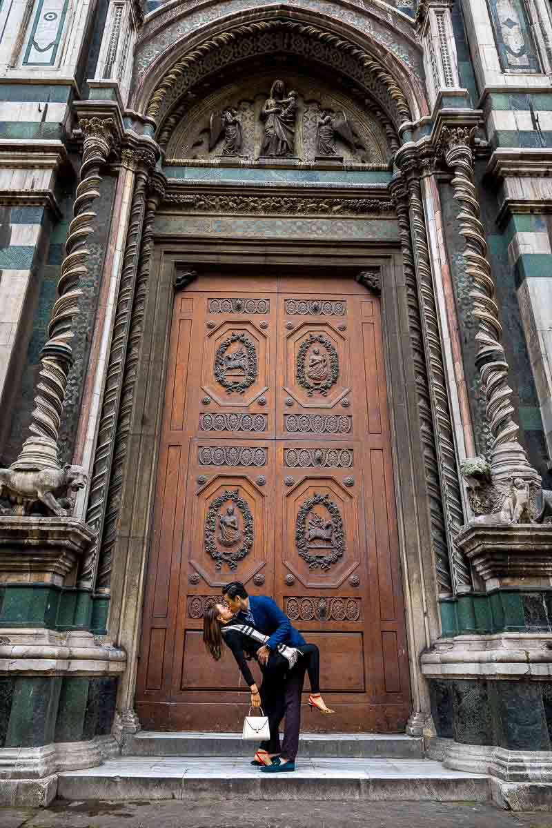 Engagement photo session posing a dip right in front of a large massive wooden door side entrance to the Duomo Cathedral