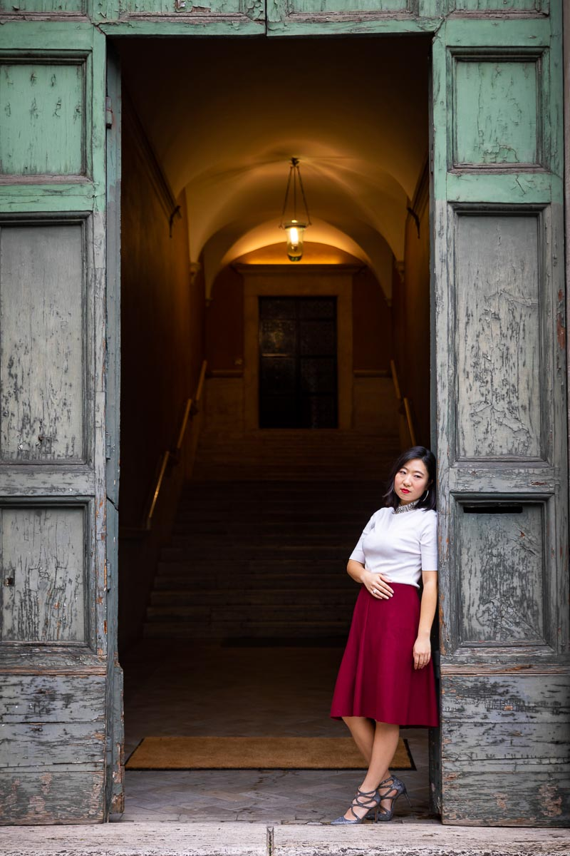 Standing underneath an ancient doorway female Rome model photography in nice natural light