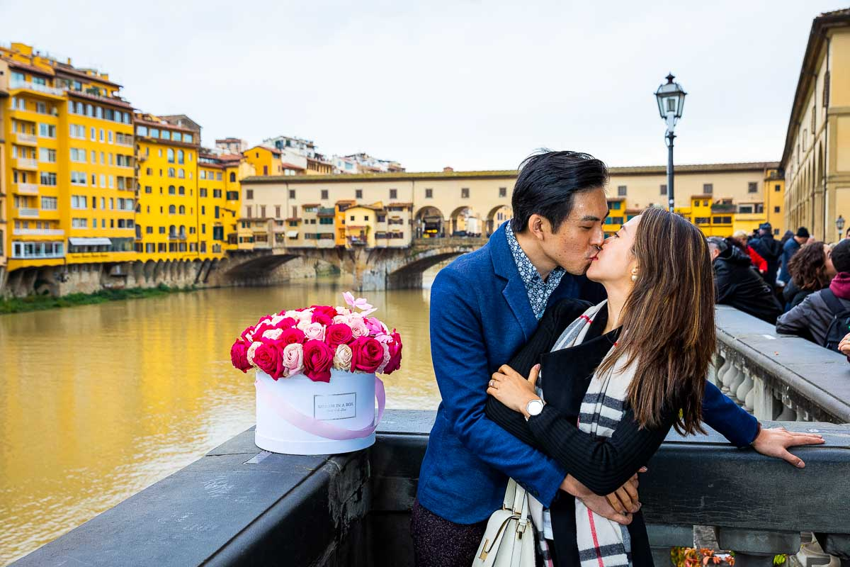 Couple kissing just engaged over the Arno river with Ponte Vecchio bridge in the far distance