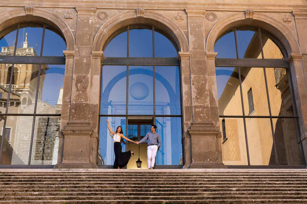 Standing on top of a large staircase posing for a photograph during a Rome couple photoshoot