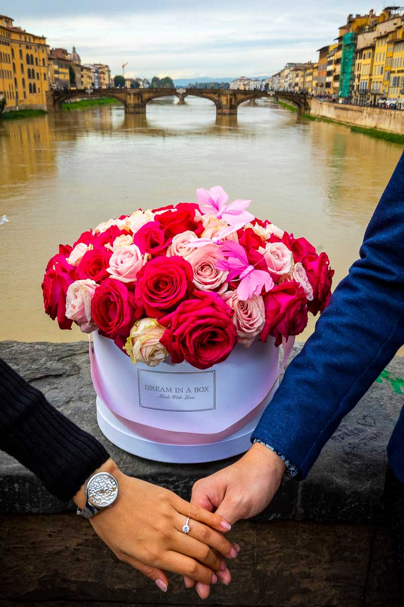 Engagement ring photo taken in Florence on Ponte vecchio over the Arno river with a beautiful bouquet of red roses in a box