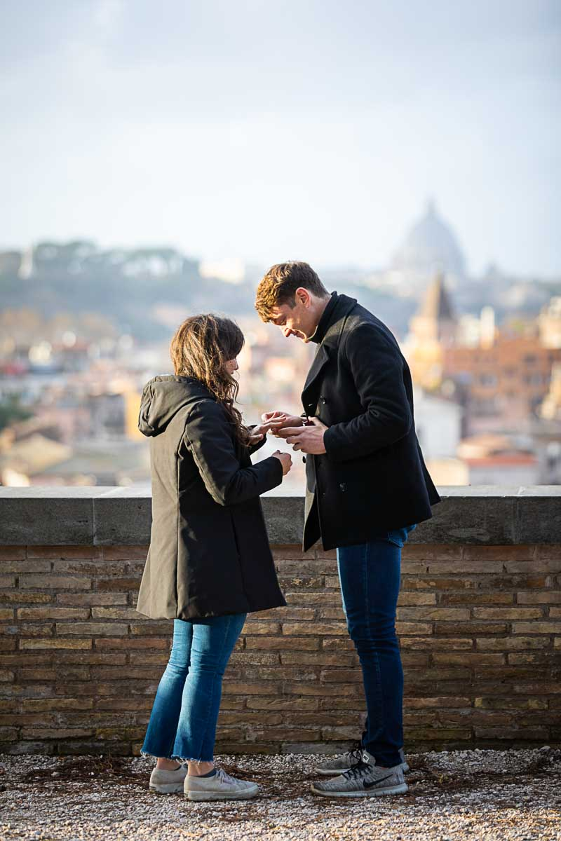 Just engaged. Putting the engagement ring on the hand before the fascinating roman view over the city