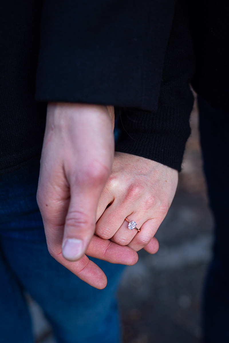 Close up image of the engagement ring holding hands