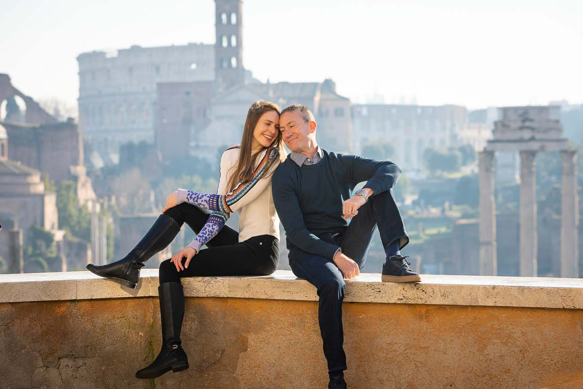 Couple sitting down on a ledge before the distant view of the roman coliseum in Rome Italy during a photoshoot