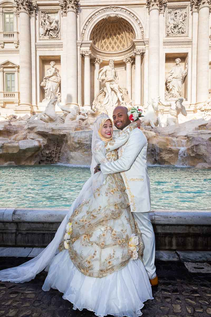 Bride and groom taking pictures together posed in the front part of the Trevi fountain. Wedding PhotoShoot in Rome