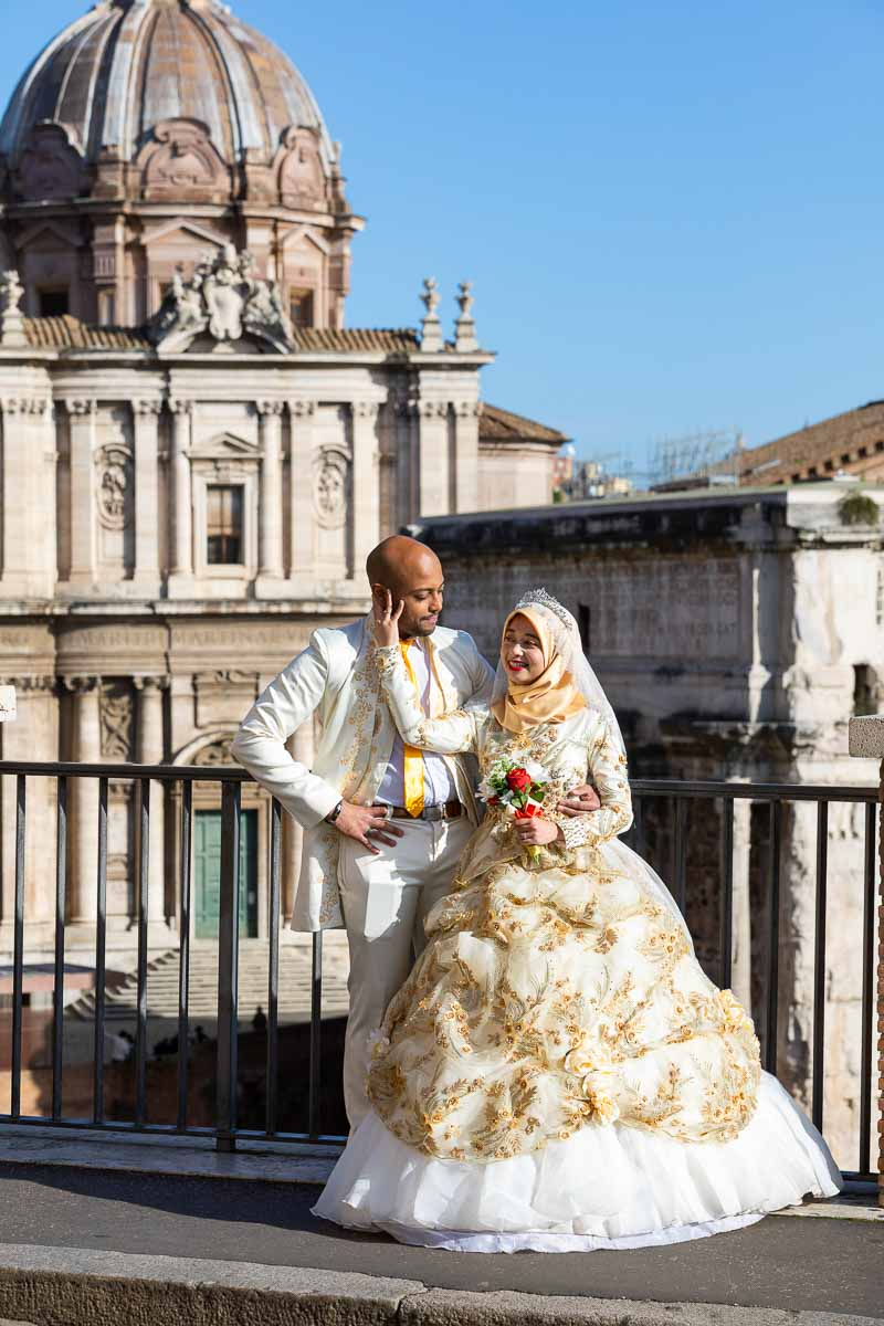 Just married couple posed in front of the ancient roman forum before ancient ruins