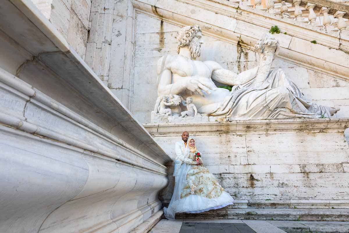 Taking newlywed pictures together under ancient roman statue in white marble