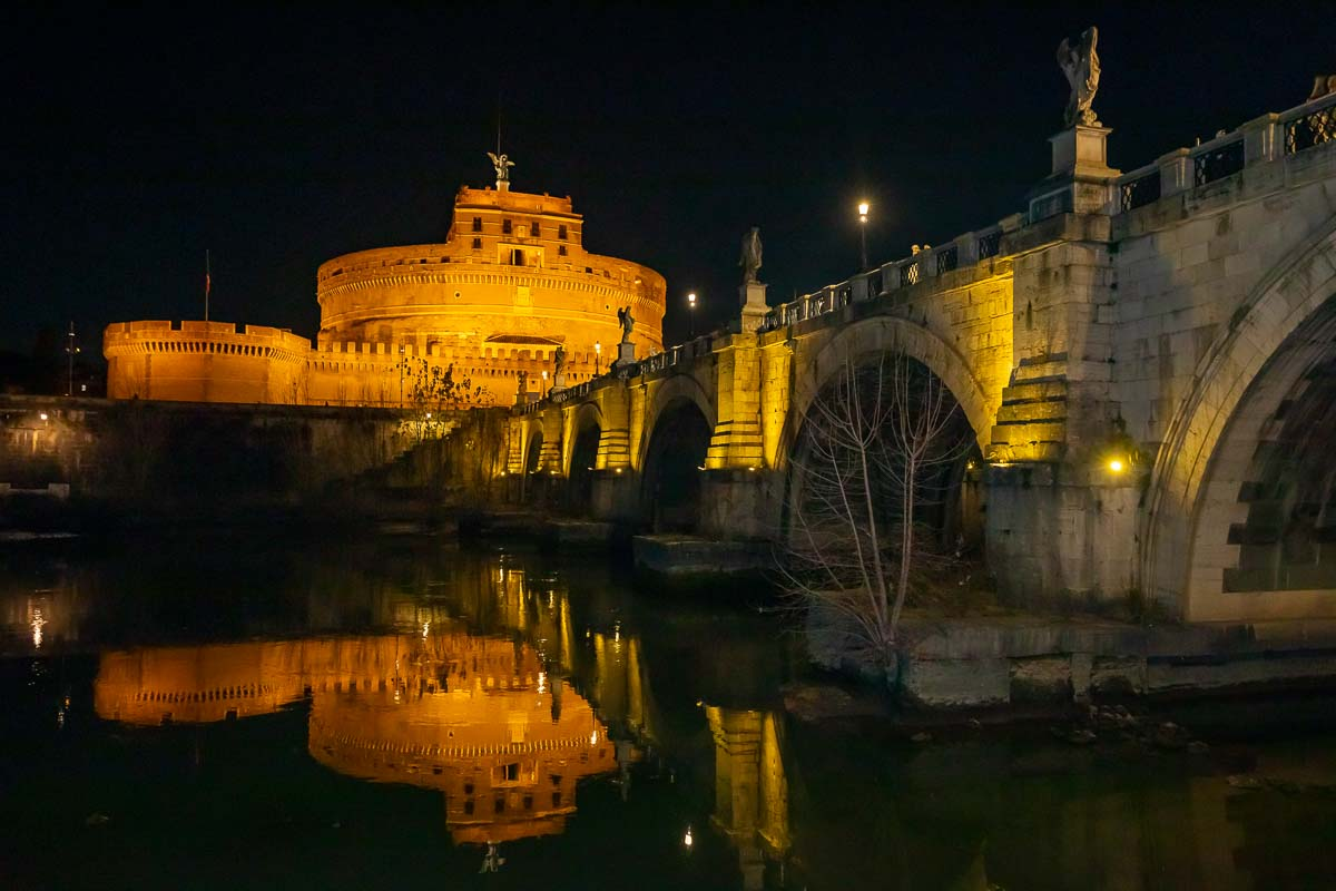 The Castel Sant'Angelo and bride seen at night from down below by the river tevere in Rome