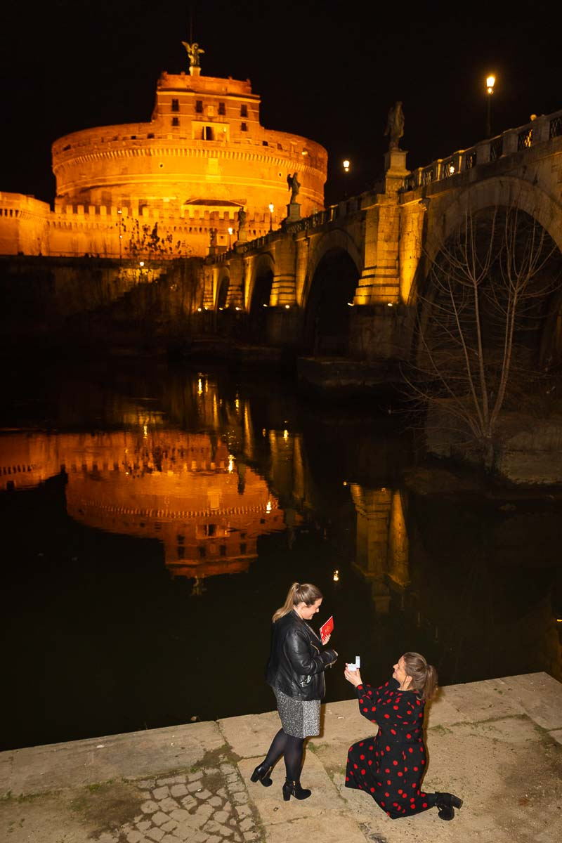 Same sex surprise wedding proposal knee down before the beautiful roman nighttime view