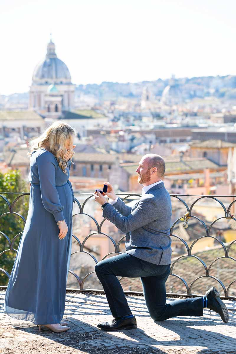 Man kneeling down for a romantic wedding marriage proposal overlooking the stunning city of Rome from the above Pincio terrace outlook