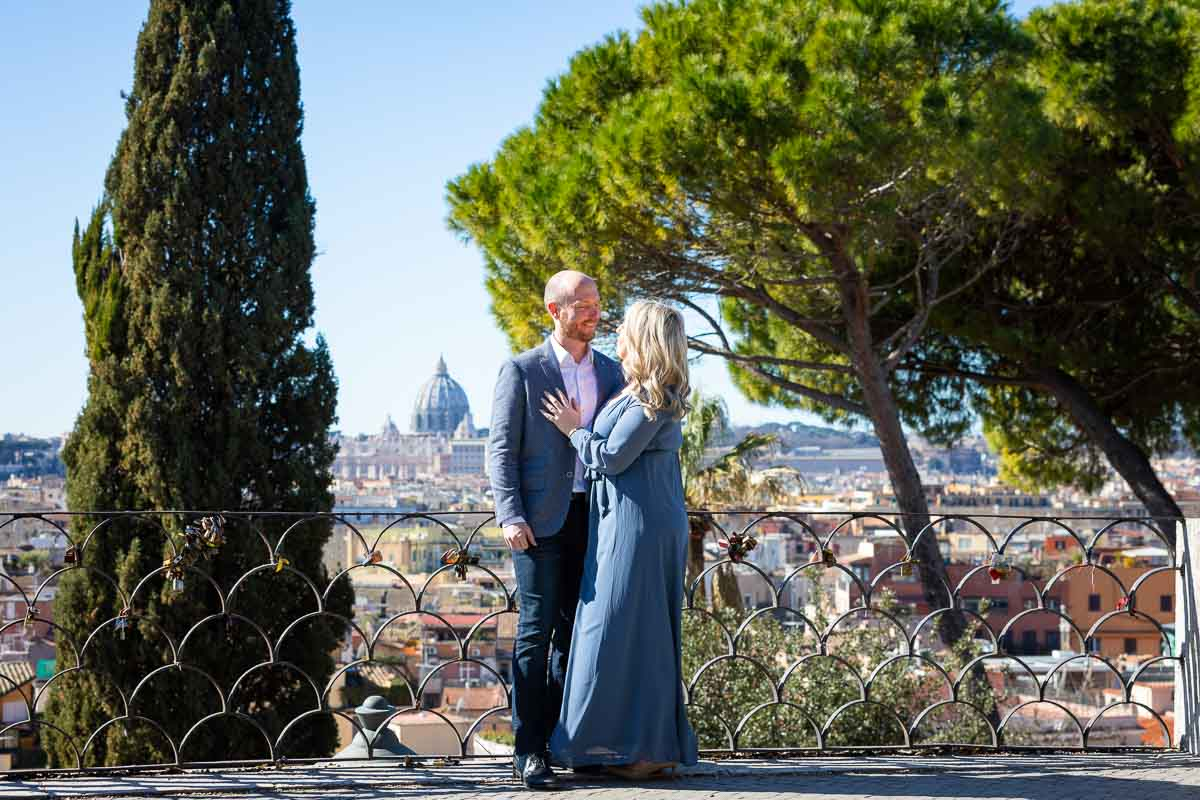 Couple standing together with Saint Peter's dome cathedral in the far distance in front of Mediterranean stone pine trees. Surprise Engagement Rome